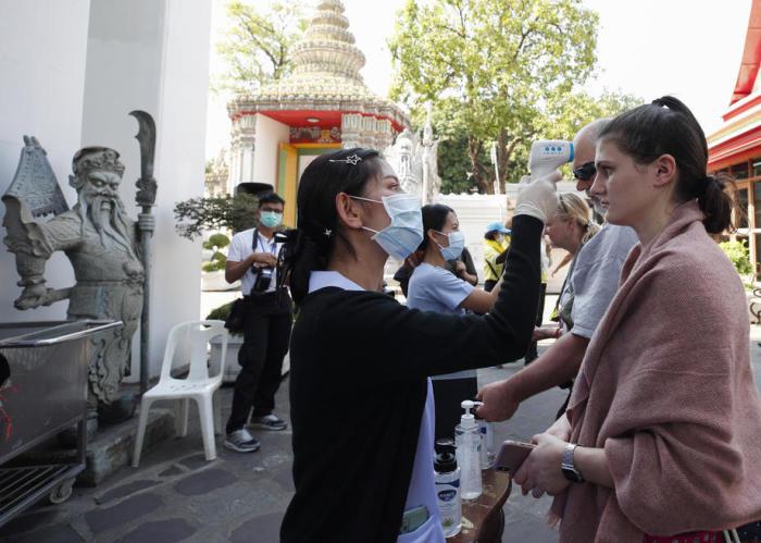 Un responsable de la santé au Wat Pho à Bangkok vérifie la température des touristes qui souhaitent visiter le temple. Photo: epa / Rungroj Yongrit